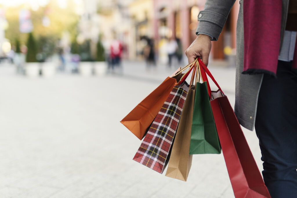 Man holding shopping bags with presents on the street